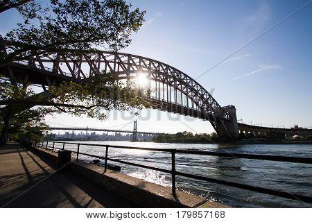 The Hell Gate Bridge and Triborough bridge with the sun, Astoria park, New York