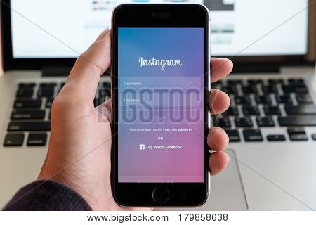 CHIANG MAI THAILAND - JAN 16 2017: A man holds Apple iPhone with Instagram application on the screen. Instagram is a photo-sharing app for smartphones. with people meeting background
