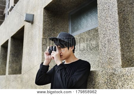 Asian guy takes photo with camera