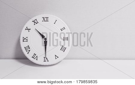 Closeup white clock for decorate show half past ten o'clock or 10:30 a.m. on white wood desk and wallpaper textured background in black and white tone with copy space