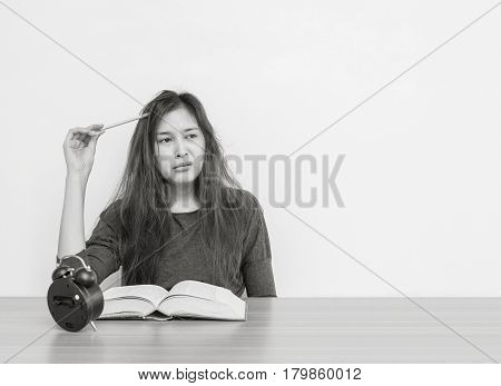 Closeup asian woman tired from reading a book with boring face emotion in work concept on wood table and white cement wall textured background in black and white tone with copy space