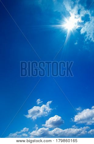 cloudscape image of clear blue sky with shining sun.