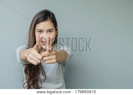 Closeup asian woman holds up one finger in two hand point to in front of her with smile face emotion on blurred cement wall textured background with copy space