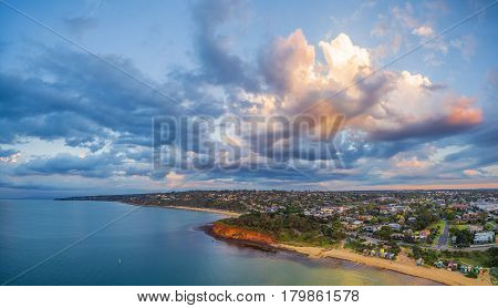 Aerial Panorama Of Coastline, Beaches And Australian Suburban Area At Sunset With Beautiful Clouds.