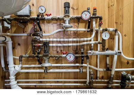 Heating system's cooper pipes with ball valves and manometer on wooden wall in home toilet