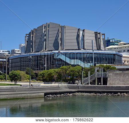 Vertical panoramic view of the Wellington Town Hall Building with a sea water lagoon and pedestrian walkway in the foreground on a Spring day.