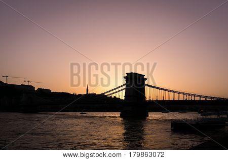 Budapest's Szechenyi Chain Bridge and skyline backlit from the setting sun.
