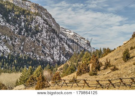 Buck and rail fence with mountains and a blue sky with clouds