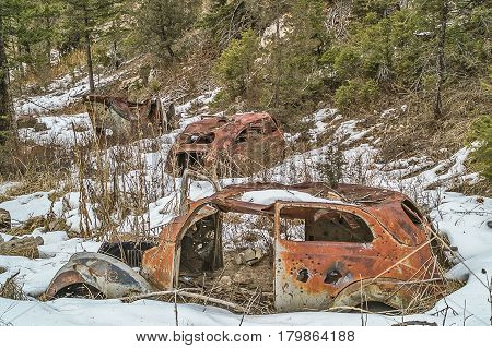 Rusty old vehicles sitting at the bottom of a hill being used for target practice