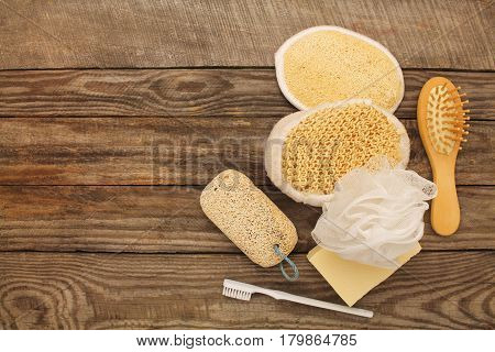 Hygiene products: soap,comb, sponge, toothbrush, pumice stone on old wooden background. Top view. Toned image.