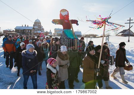 Kazan, Russia - 28 february 2017 - Sviyazhsk Island : Russian ethnic carnival Maslenitsa - The pancake week, Shrovetide, the crowd carries the effigy of winter to burn - top view, snow sunny day