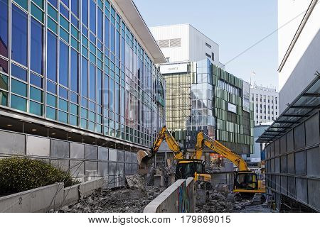 PADERBORN GERMANY MARCH 13 2017: Construction site in the inner city with two excavators between mirrored department store houses