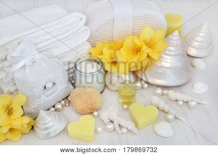 Aromatherapy spa treatment products with moisturizer, essence, freesia flowers, shells and pearls on distressed wood background.