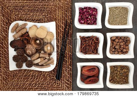 Chinese herbal medicine selection in white china dishes with chopsticks.