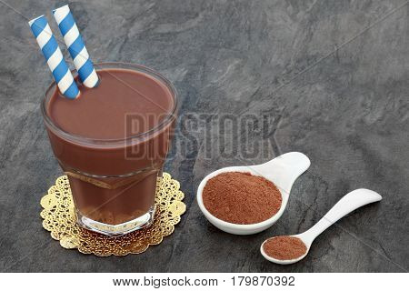 Chocolate whey protein powder drink in a glass with supplement powder in a china bowl and spoon. Used  by body builders.