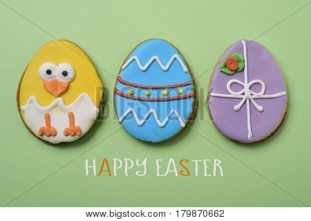 the text happy easter and some different handmade cookies patterned as decorated easter eggs and as a funny chick on a green background