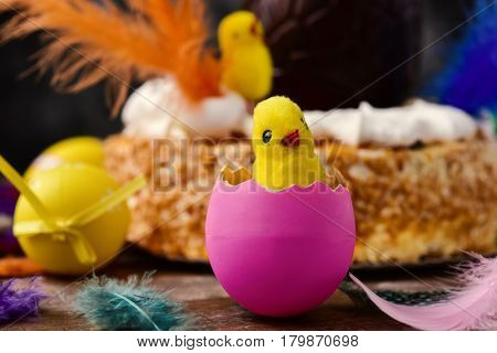 closeup of a toy chick emerging from a pink egg, some easter eggs and feathers of different colors on a wooden surface and a mona de pascua, a cake eaten in Spain on Easter Monday, in the background