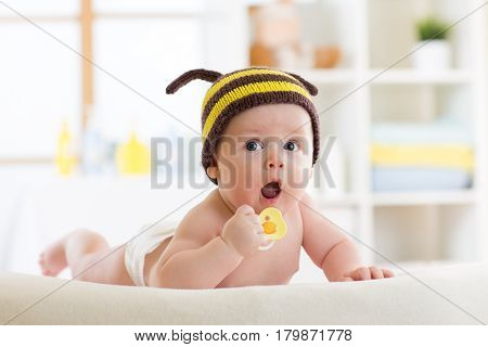 Cute baby wered funny knitted hat with pacifier on the bed at home