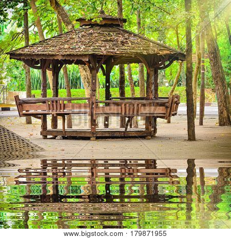 Wooden Garden Gazebo in public park near water poor