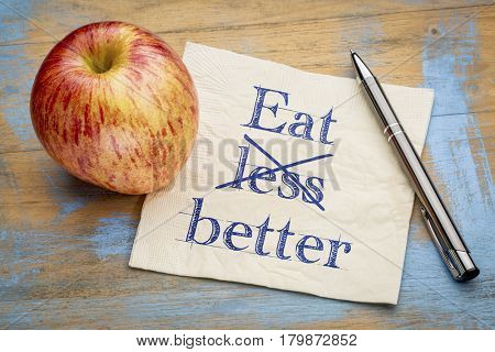 Eat better, not less  - handwriting on a napkin with a fresh apple