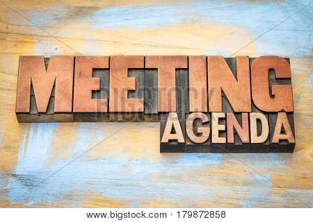 meeting agenda banner in letterpress wood type against grunge wooden background
