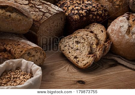 Many different handmade, freshly baked breads on wooden table with copy space
