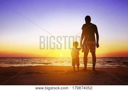Father and son standing at sunset beach. Fatherhood concept with space for text