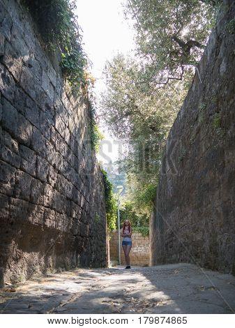 Portrait of beautiful girl posing in garden at street of Sorrento, Italy, vertical