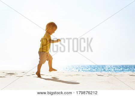 Happy baby walking ot jumping at white lonely beach on blue sea background