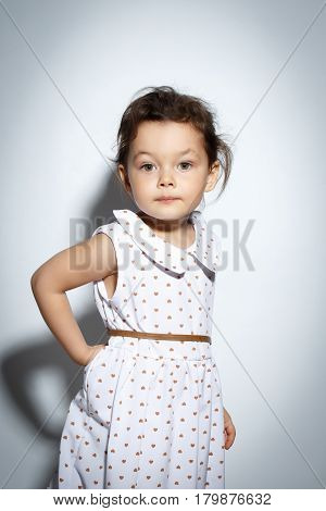 Portrait of 3 year old little girl with dress, posing on bright white background