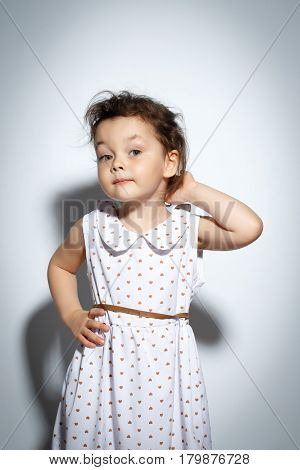 Portrait of 3 year old little girl with dress, posing touching hair on bright white background