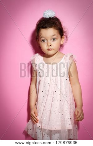 Portrait of Sad 3 year old little girl with dress, on bright pink background