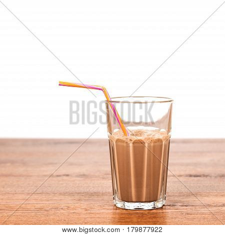Faceted glass of cold cocoa on a wooden table closeup