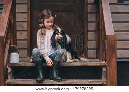kid girl playing with her spaniel dog, sitting on stairs at wooden log cabin