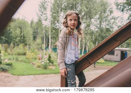 kid girl playing at wooden cabin in the woods. Child spending summer vacation outdoor at country house
