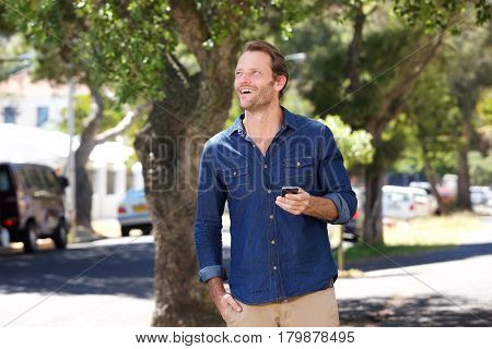 Handsome Guy Walking Outside With Mobile Phone