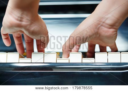 Scene of pianist hands from underneath angle playing piano.