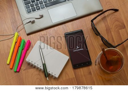 Nitra, Slovakia, april 3, 2017: Adobe Acrobat Reader application in a mobile phone screen. Workplace with a laptop, an earphones, notepad, pen, tea, sunglasses and color markers on wooden background