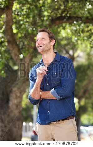Attractive Man Smiling Outdoors And Looking Up