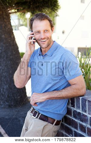 Handsome Man Smiling Outdoors With Mobile Phone