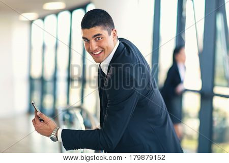 Businessman holding a phone looking at camera smiling