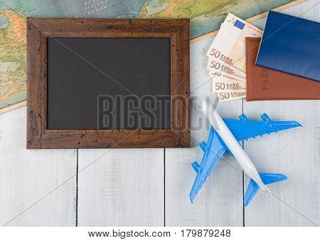 Blank Blackboard, Plane, Map, Passport, Money On White Wooden Table