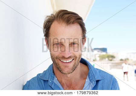 Close Up Smiling Man Leaning Against Wall Outside
