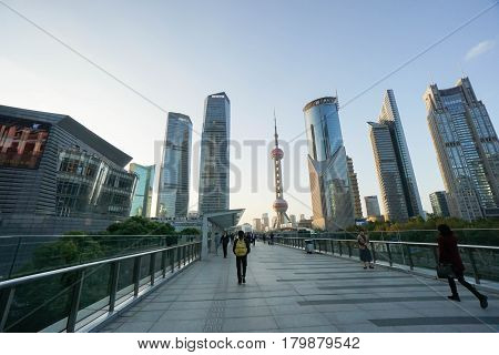 people walk on concrete pavement to Oriental Pearl Tower taken in Shanghai China on 25 November 2016