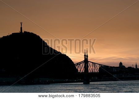 With the sun setting over Budapest the Elisabeth Bridge and Liberty Statue are silhouetted by the golden light.
