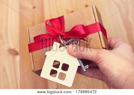 Holiday gift with the symbols of the house and key in hand on a wooden background / congratulation with the housewarming party