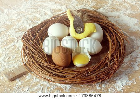 eggs with a toy bird lying in a wreath on a table strewn with flour / Easter cooking