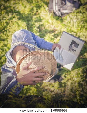 Teenager reads placidly next to the shade of the tree