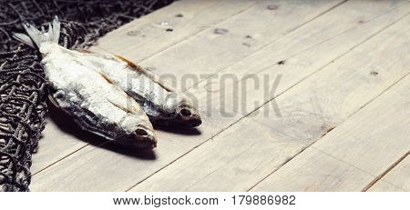 Fishing nets and dried fish on the wooden background.