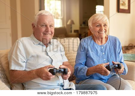 Happy senior couple sitting together on their living room sofa holding controllers and laughing while playing a video game